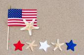 American flag with starfishes on the sandy beach — Stock Photo