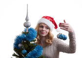 Beautiful girl decorates a Christmas tree — Stock Photo