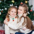 Girls near the Christmas tree with gifts — Stock Photo #62280581