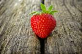Ripe red strawberry on a wooden background — Stok fotoğraf