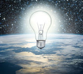 Light bulb over Earth on a background of the universe — Stock Photo