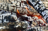 Charred wood burning down in the fire glow, close-up — Stock Photo