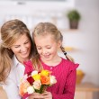 Girl giving flowers to her mother — Stock Photo #52287109