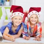 Girls in Santa hats drawing — Stock Photo #52747943