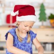 Girl with santas hat baking cookies — Stock Photo #52748919