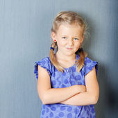 Girl with arms crossed grimacing — Stock Photo
