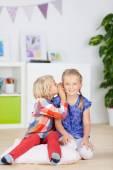 Girl smiling while sister whispering secret — Stockfoto