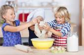 Sisters putting dough in bowl — Stock Photo