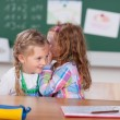 Girl whispering to friend in school — Stock Photo #53241359