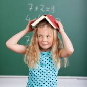 Girl balancing book on her head — Stock Photo