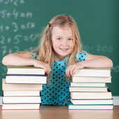 Blond girl in school with her books — Foto de Stock
