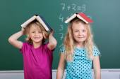 Two little schoolgirls with book hats — Stock Photo
