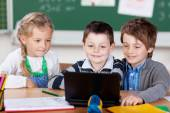 Three young schoolchildren using laptop — Stockfoto