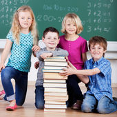 Schoolchildren with tall stack of books — Stock Photo