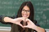 Smiling girl making heart gesture — Stock Photo