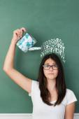 Student pouring interrogation signs over her head — Stockfoto
