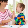 Young boy laughing with his mother or teacher — Stock Photo #54599617