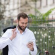 Smiling Handsome Man Using Phone While Walking — Stock Photo #55783467