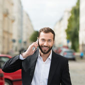 Happy attractive businessman on his mobile phone — Stock Photo
