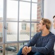 Couple sitting looking out of an urban apartment — Stock Photo #56432725