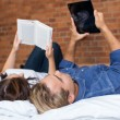 Couples Lying on Bed with Book and Tablet — Stock Photo #56435743