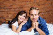 Smiling Young Sweethearts Lying on Bed — Stockfoto