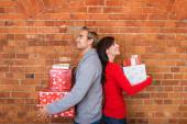 Smiling Couple Holding Gifts in Back to Back — Stock Photo