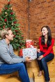 Man presents girlfriend Christmas present — Stock Photo