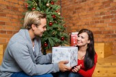 Man presents girlfriend Christmas present — Stock fotografie