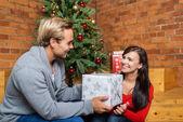 Man presents girlfriend Christmas present — Stok fotoğraf