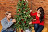 Couple decorating christmas tree — Stock Photo