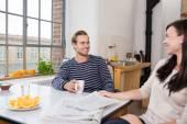 Couple talking to kitchen table — Stock Photo