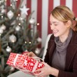 Woman opening Christmas present — Stock Photo #58664455
