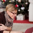 Woman with laptop in front of Christmas tree — Stock Photo #58665711