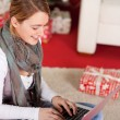 Woman Using Laptop Near Gift Box — Stock Photo #58665811