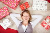 Woman surrounded with Christmas gifts — Stock Photo