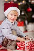 Little boy unwrapping Xmas gift — Stock Photo
