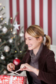 Woman unwrapping her Christmas gift — Stock Photo