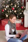 Woman with laptop near Christmas tree — Stock Photo