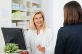 Pharmacist helping customer in pharmacy — Stock Photo