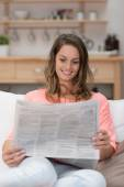 Young woman reading newspaper — Stock Photo