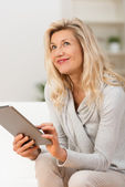 Woman using tablet sitting thinking — Stock Photo