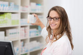 Smiling pharmacist promoting product — Stock Photo