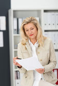 Middle-aged businesswoman checking paperwork — Stock Photo