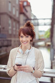 Joyeuse fille tenir téléphone tout en les balustrades — Photo