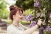 Cute Girl Smelling Pretty Purple Flowers — Stock Photo