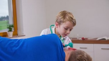 Child checking patient's ear. — Stockvideo