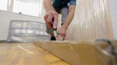 Man Cutting through long box — Stock Video