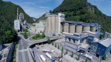 Big factory between green hills — Stock Video