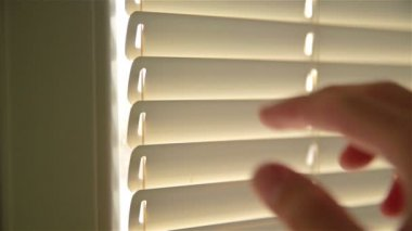 Man Looking through roller blind — Stock Video